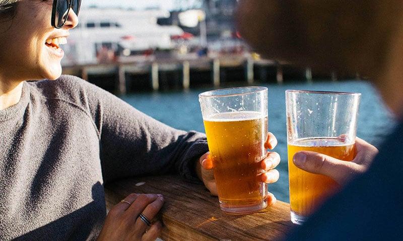 couple-enjoying-beer-near-ocean