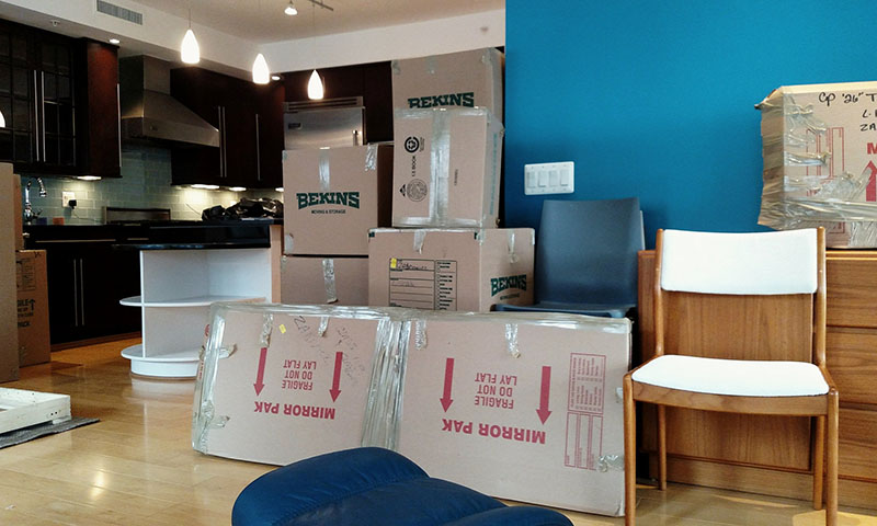 Packing boxes in living room with tape