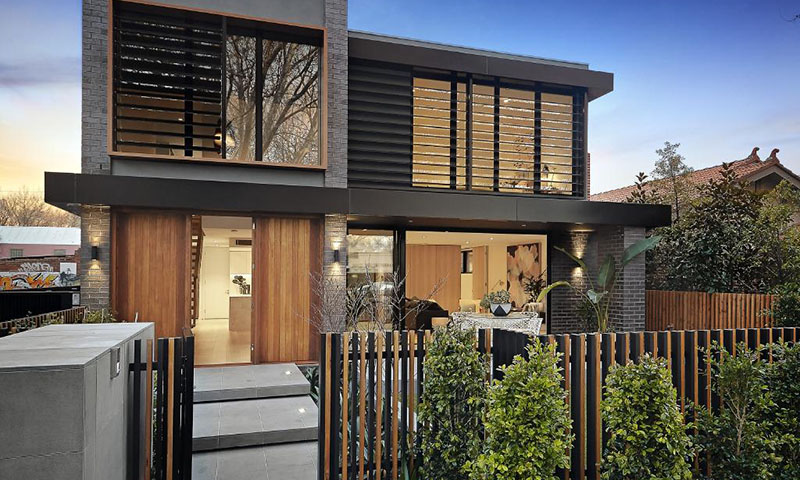 Beautiful modern home exterior with wooden fence