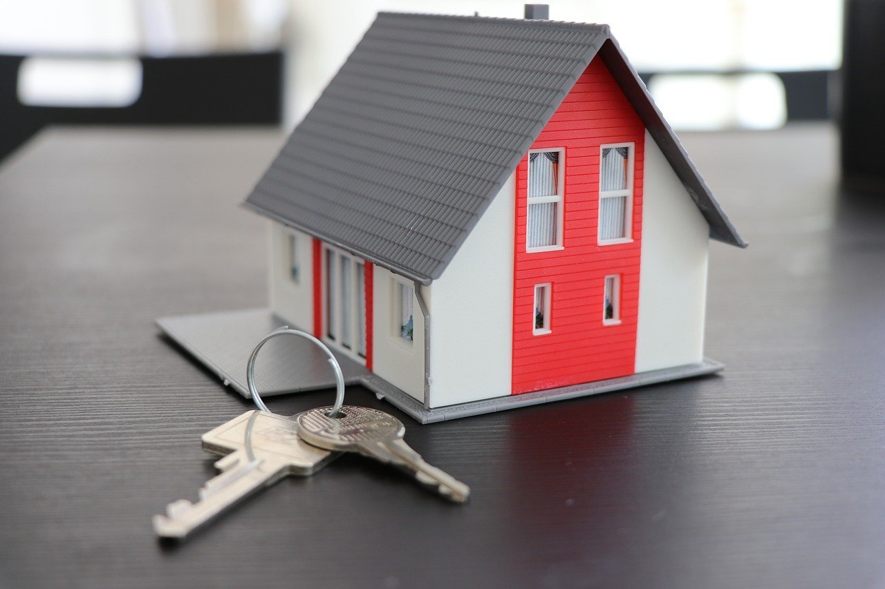 A model of a home with keys symbolizing the selling process.