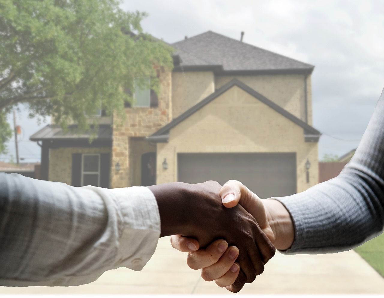 People shaking hands after closing the home selling deal.