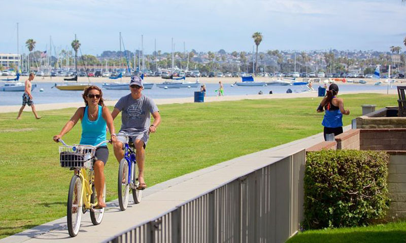 Couple riding bicycles along mission bay San Diego