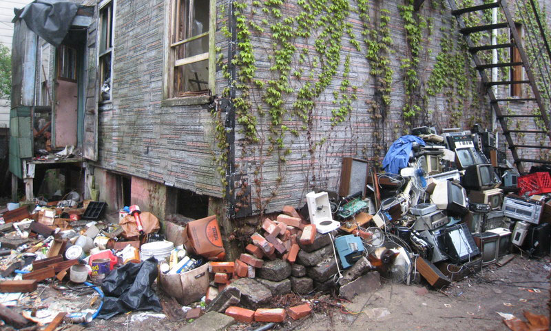 External hoarder home surrounded by mess