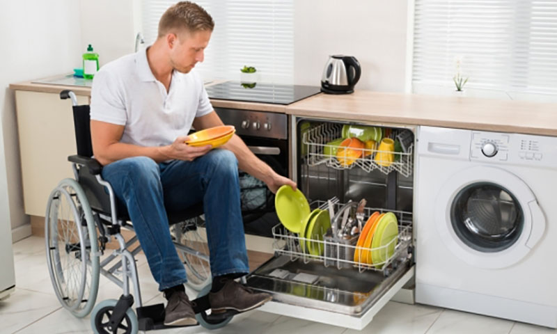 Man in wheelchair doing his dishes in his home kitchen