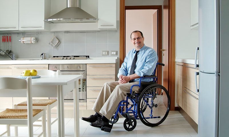 Happy home owner with disability in wheelchair in kitchen