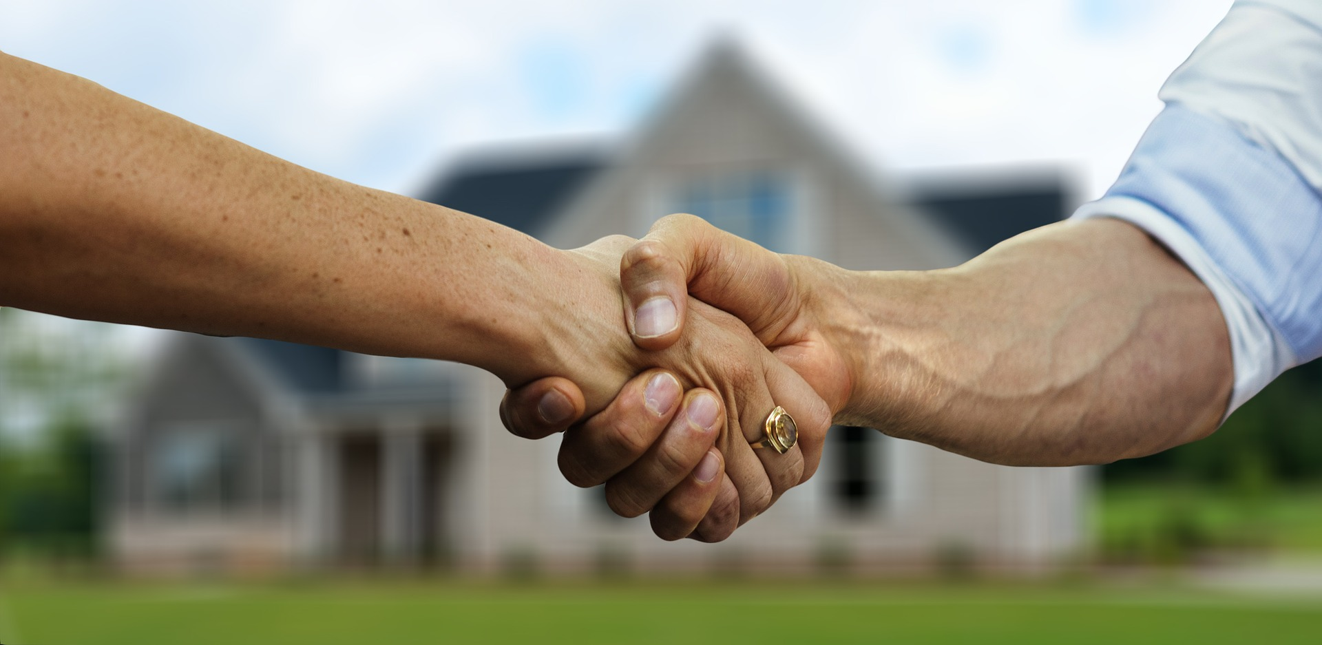 Real estate agent shaking hands with client in front of new home