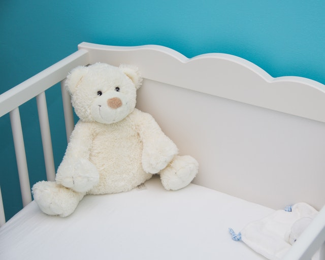 A plush teddy bear in baby's crib